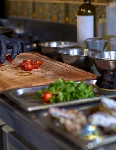 Food concept. The chef cuts the tomatoes, prepares the ingredients for the dish on the table in the kitchen.